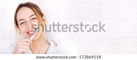 Happy young woman brushing teeth .