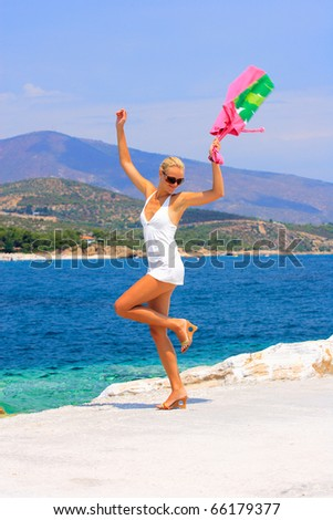 Happy young woman by the sea with beach bag in her hand