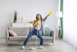 Happy young woman cleaning her home, singing at mop like at microphone and having fun, free space. Millennial housewife enjoying domestic chores, doing home cleanup creatively