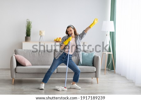 Happy young woman cleaning her home, singing at mop like at microphone and having fun, free space. Millennial housewife enjoying domestic chores, doing home cleanup creatively Stock photo ©