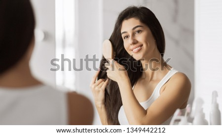 Happy young woman combing her hair and smiling looking at the mirror. Everyday haircare concept