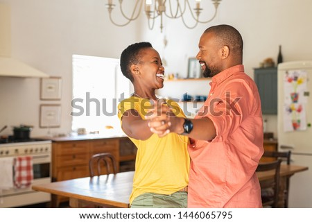 Happy young woman dance with her husband as they celebrate a special day at home. Young african couple dancing and laughing at new home. Mature couple having fun together while dancing in kitchen.