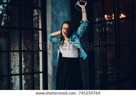 Happy young woman dancing while listening favourite music in modern earphones connected to smartphone.Stylish cheerful female in optical eyeglasses singing new song enjoying free time outdoors