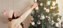 Happy young woman decorates the Christmas tree hang the ball on the tree. Christmas decoration, toys hanging on the tree, Christmas tree ball. New year and christmas holiday concept