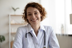 Happy young woman doctor wears white medical coat and stethoscope looking at camera. Smiling female physician, general practitioner consult patient online by video call. Close up head shot portrait