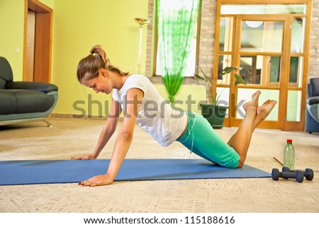 Happy young woman doing fitness at home. Healthy life.