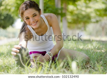Happy young woman doing some stretching exercises at the park