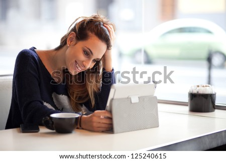 Happy young woman drinking coffee / tea and using tablet computer in a coffee shop