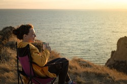 Happy young woman drinking hot coffee from iron mug cup,sitting in touristic chair on cliff in front of the sea.Enjoying sunset scenery view of nature landscape.Trekking camping and adventure concept