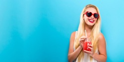 Happy young woman drinking smoothie on a solid background