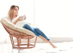 Happy young woman drinking tea while sitting in armchair at home