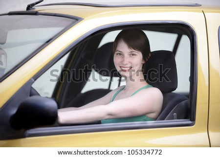 Happy young woman driving her new car