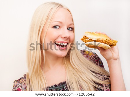 happy young woman eating a hamburger with chicken,  isolated against white background