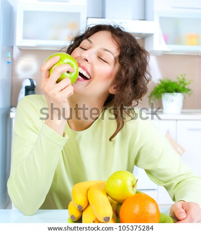 Happy Young Woman Eating Apple on Kitchen .Diet.Dieting concept.Health