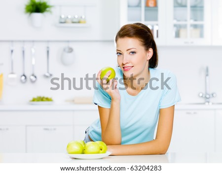 Happy young woman eating apples on kitchen