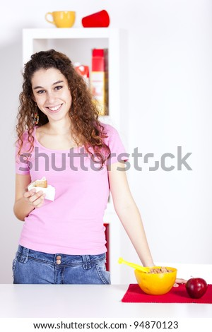 Happy young woman eating breakfast