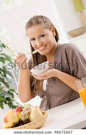 Happy young woman eating breakfast cereal and drinking orange juice, smiling.
