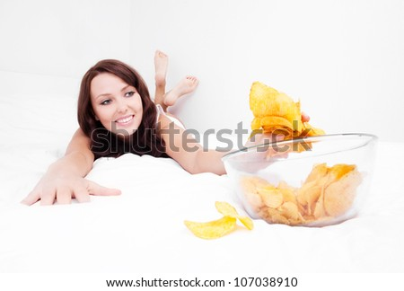 happy young woman eating potato chips in bed at home
