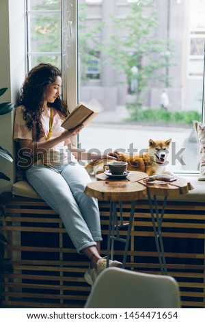 Happy young woman enjoying book and petting dog sitting on window sill in modern cafe. Literature, youth culture and lifestyle, domestic animals concept.