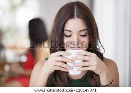 Happy young woman enjoying coffee at a restaurant