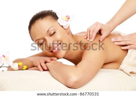 Happy young woman enjoying massage treatment isolated on white background - stock photo