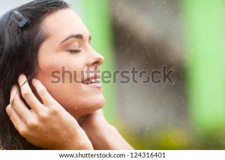 happy young woman enjoying rain falling on her face #124316401