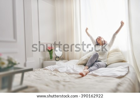 Shutterstock Happy young woman enjoying sunny morning on the bed