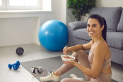 Happy young woman enjoys regular fitness exercise and well-balanced diet. Positive smiling female sitting on sports mat after routine workout at home, eating healthy natural food and looking at camera