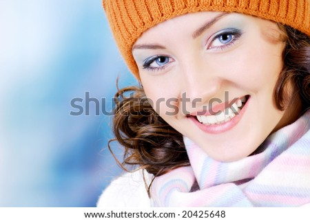 Happy young woman face with beauty smile dressed in the winter hat, scarf. People winter concept.