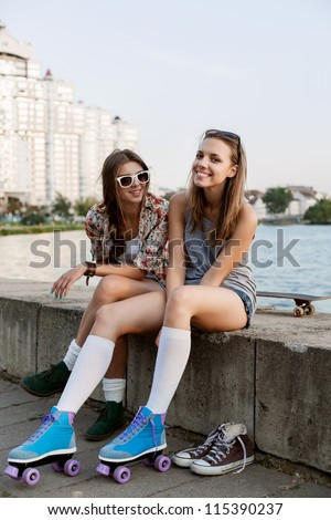 happy young woman fastening the roller skates and is getting ready to ride  in the park, outdoors