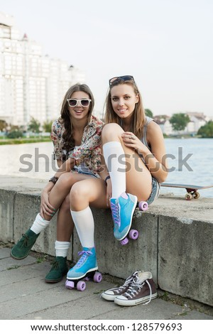 happy young woman fastening the roller skates and is getting ready to ride, outdoors