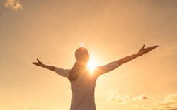 Happy young woman feeling free with arms up looking to the sky.