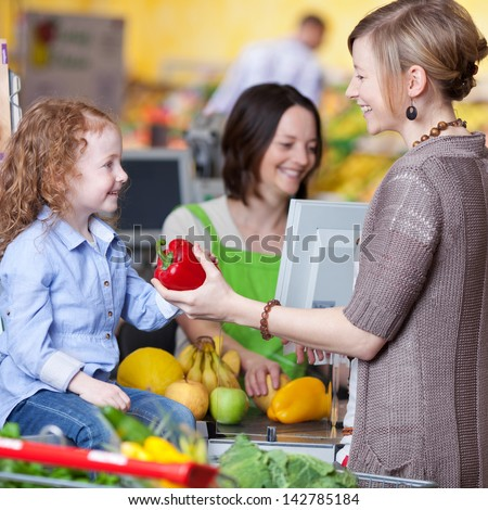 Happy young woman giving capsicum to daughter with cashier smiling in background at super market