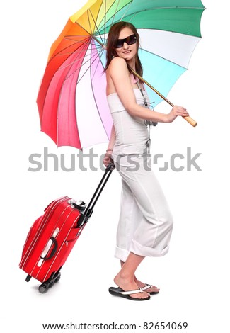 Happy young woman going on vacations with her suitcase and rainbow umbrella.