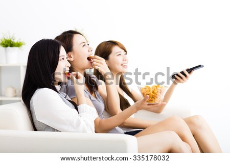 happy young woman group  eating snacks and watching the tv