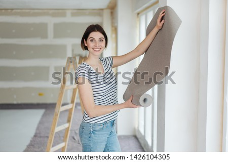 Happy young woman hanging wall paper while doing DIY home renovations standing in front of a newly painted section of wall holding a roll up on display Stockfoto ©