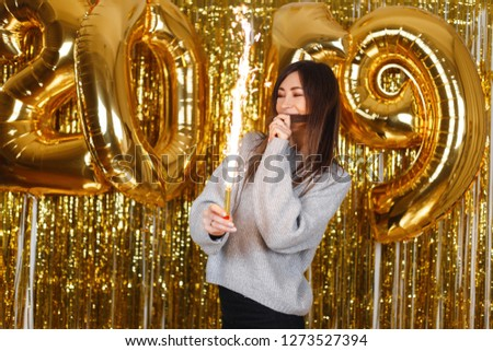 Happy young woman happily holds in her hands fireworks on the background of balloons 2019. The girl celebrates the New Year. Magical celebration atmosphere.