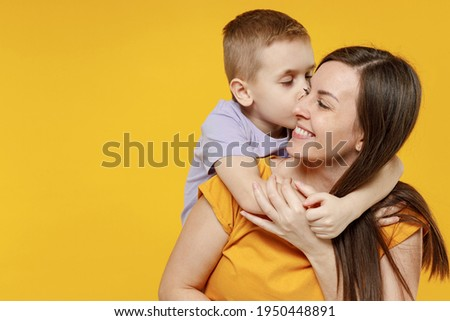 Happy young woman have fun with cute child baby boy 5-6-7 years old in violet t-shirt. Mommy little kid son posing together hugs isolated on yellow background studio. Mother's Day love family concept