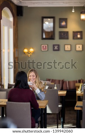 Happy young woman having coffee with friend at coffeeshop