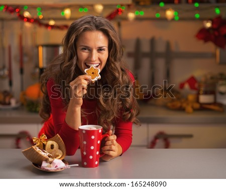 Happy young woman having eating christmas cookies in kitchen - stock photo