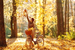 Happy young woman having fun and playing with autumn yellow leaves in autumn park.  Relaxation, enjoying, solitude with nature.