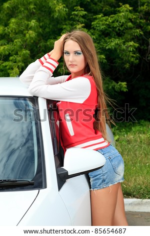 Happy young woman having summer trip on a car.