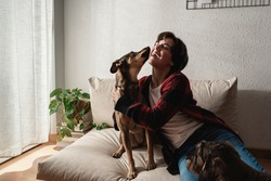 Happy young woman having tender moment with her dogs at home - Focus on face