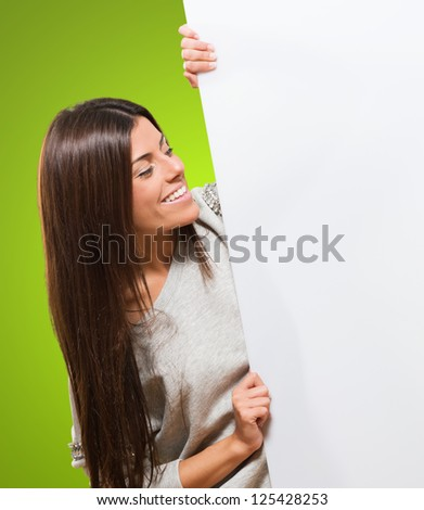 Happy Young Woman Holding A Blank Card against a green background