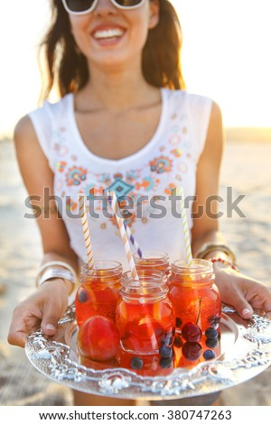Happy young woman holding a dish with a drinks at summer beach party - stock photo