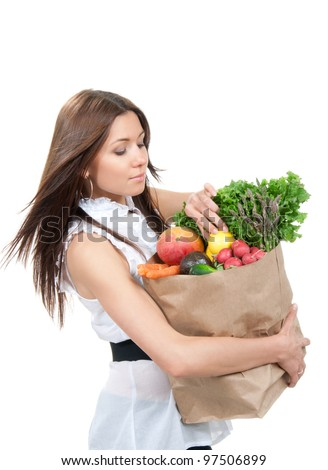Happy young woman holding a grocery shopping bag full of groceries, mango, salad, asparagus, radish, avocado, lemon, carrots on white background