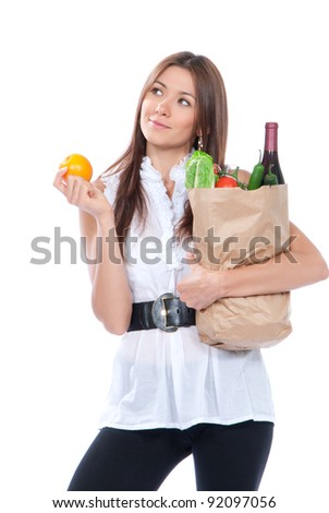 Happy young woman holding a paper shopping bag full of groceries, mango, salad, asparagus,tomatoes, pepper, orange, bottle of wine on white background