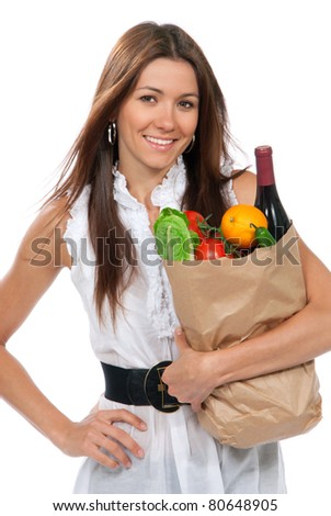 Happy young woman holding a paper shopping bag full of groceries salad, green pepper, tomatoes, orange, bottle of wine isolated on white background