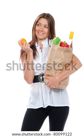 Happy young woman holding a shopping bag full of groceries, fresh salad, red pepper, bottle of wine and orange in hand isolated on white background