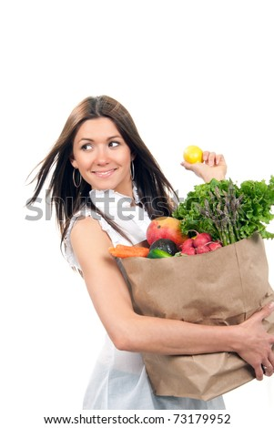 Happy young woman holding a shopping bag full of groceries, mango, salad, asparagus, radish, avocado, lemon, carrots on white background